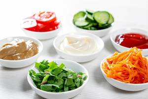 White bowls with sauces, herbs and vegetables