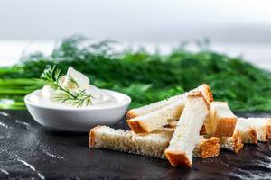 White bread snacks with sauce and herbs