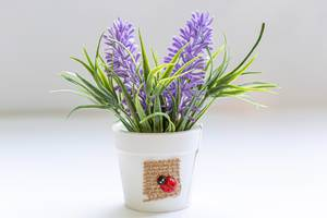 White bucket with purple artificial flowers