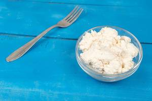 White Cheese in the bowl on the blue wooden table