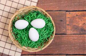 White chicken eggs in a basket on a wooden table