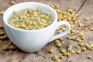 White cup of chamomile tea with dry chamomile flowers on a wooden background