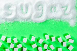 white granulated sugar and refined sugar on a green background with the inscription