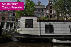 White House boat next to title Amsterdam Canal Parade, that parts in the annual  LGBTQ Amsterdam Pride Parade