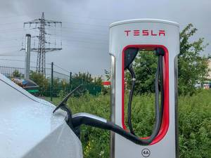 White Tesla Model 3 refuels at a Supercharger - charging station in rainy weather