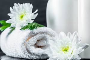 White towel and white chrysanthemums with bottles of cosmetics