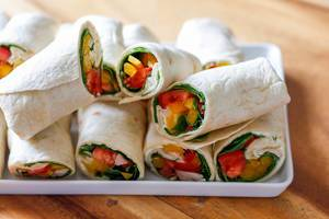 White tray with vegetable and chicken wraps