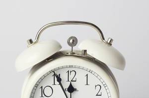 White vintage alarm clock close up with the symbolising time 5 before 12