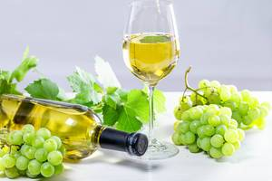 White wine in a glass with a full bottle, grapes and leaves on a white wooden background (Flip 2019)