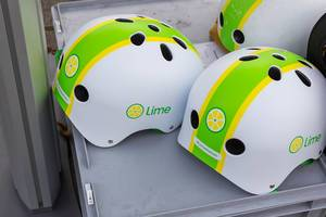 White, yellow and green helmets with the logo of the e-scooter sharing brand, Lime