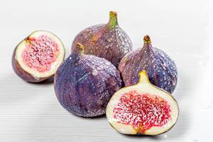 Whole and halves of fresh figs with water drops on white wooden background (Flip 2019)