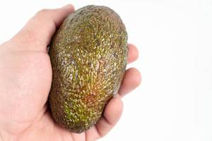 Whole-Avocado-in-the-hand-above-white-background-with-copy-space.jpg