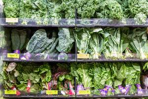Whole Foods Supermarket shelf filled with green organic salad leaves, kale, red and organic rainbow chard