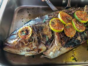 Whole grilled fish decorated with lime slices and sweet pepper
