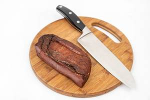 Whole piece of Smoked Ham on the wooden cutting board