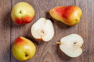 Whole ripe pears and halves on a wooden table. Top view (Flip 2019)