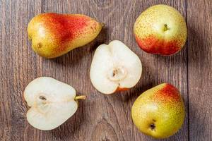 Whole ripe pears and halves on a wooden table. Top view