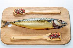 Whole smoked mackerel on a wooden kitchen Board with a mix of peppers. Top view (Flip 2019)