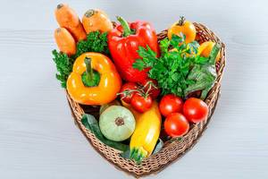 Wicker basket in the shape of a heart filled with fresh vegetables and herbs (Flip 2019)