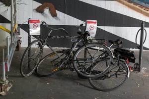 Widerrechtlich angekettete Fahrräder und eine Info-Zettel über kostenpflichtige Entfernung