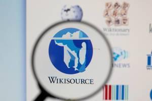 Wikisource-Logo am PC-Monitor, durch eine Lupe fotografiert