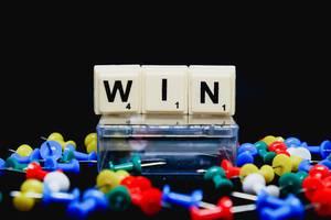 Win (Gewinnen) Text mit Reißzwecken auf schwarzem Untergrund