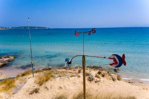 Wind chime with compass - direction indicator in the white sandy beach before the wide Aegean Sea