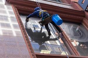 Window cleaner attached to a rope system cleans the windows of a building in Chicago