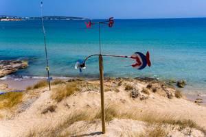 Windspiel mit Himmelsrichtungsanzeige, im weißen Sandstrand vor dem weiten Meer in der Ägäis