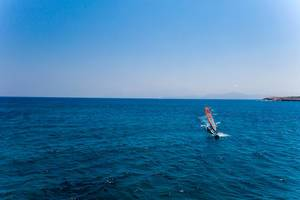 Windsurfer on the deep blue sea, in front of the Santa Maria beach of Paros, Greece