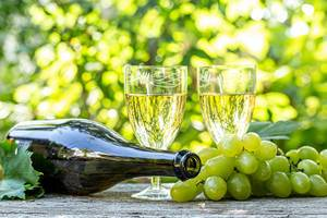 Wine in glasses with a bottle and fresh grapes on a blurred bokeh background of nature