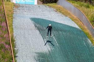 Winter sportsman trains ski jumping in summer at the ski jumping facility of Lahti, Finland
