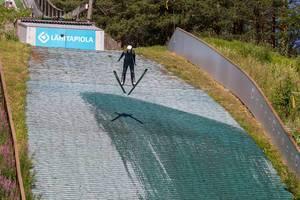 Wintersportler trainiert das Skispringen im Sommer in der Schanzenanlage von Lahti, Finnland