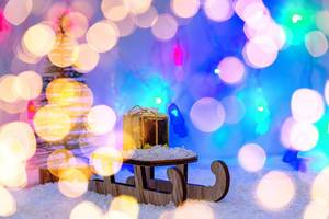 Wintervorbereitung und Ferien - Schlitten mit einem Geschenk und Schnee und verschwommenem Licht