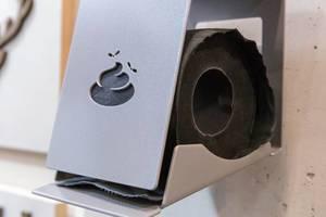 Witziger Toilettenpapierhalter mit Motiv in Form von Häufchen mit Fliegen mit schwarzem Papier