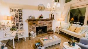 Wohnzimmer eines privaten Gästehauses mit offenem Kamin und heller, rustikaler Einrichtung