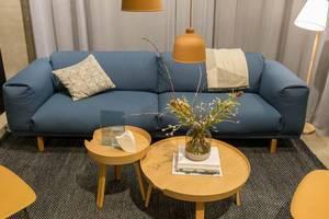 Wohnzimmerkonzept - weiches, gemütliches Sofa mit Zierkissen und runde, hölzerne Beistelltischen