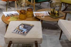 Wohnzimmertisch mit Dekoration und Hocker im Stil der 60er-Jahre mit Zeitschrift