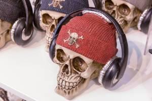 Wollmütze mit Totenkopf Schädel verziert auf einem Totenkopf Schädel mit Kopfhörern