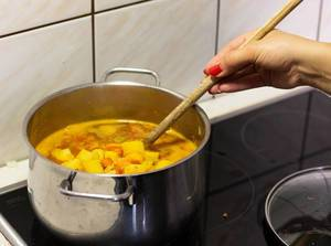 Woman cooking vegetable soup in home kitchen