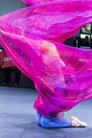Woman dancing at Photokina in Cologne covered in pink scarf