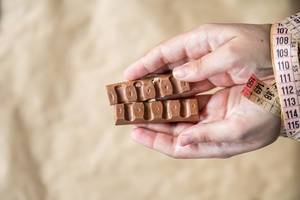 Woman hand bounded with measuring tape holding slices of sweet chocolate. Diet concept.
