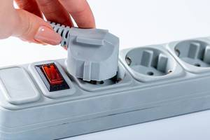 Woman hand plugging in appliance to portable socket
