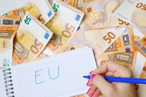 Woman hand writing EU, 50 Euro banknotes background