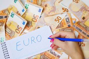 Woman hand writing Euro, 50 Euro banknotes background