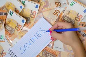 Woman hand writing Savings, 50 Euro banknotes background