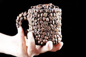 Woman holding a cup of coffee beans in her hand, black background (Flip 2019)