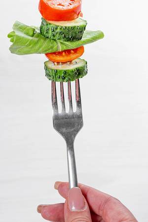 Woman holding a fork with fresh vegetables. Healthy eating concept (Flip 2019)
