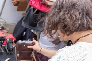 Woman inspecting second-hand cameras at the Naschmarkt flea market in Vienna