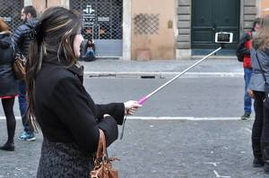 Woman is taking a selfie with a selfie stick